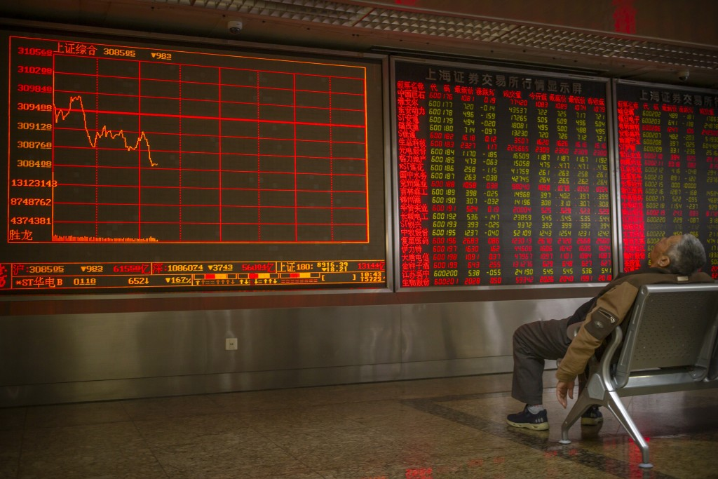 A Chinese investor rests as he monitors stock prices at a brokerage house in Beijing, Friday, Jan. 10, 2020. Asian shares rose Friday as worries reced...