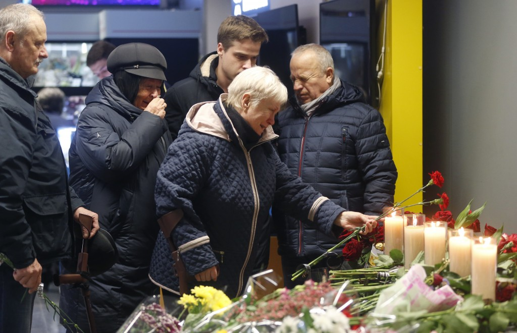 Relatives of one of the flight crew members of the Ukrainian 737-800 plane that crashed on the outskirts of Tehran, stand at a memorial inside Borispi...