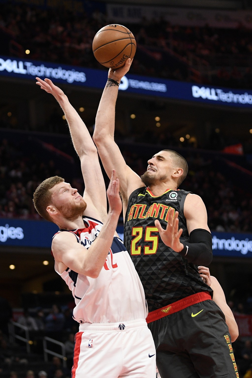 Atlanta Hawks center Alex Len (25) goes to the basket next to Washington Wizards forward Davis Bertans (42) during the first half of an NBA basketball...