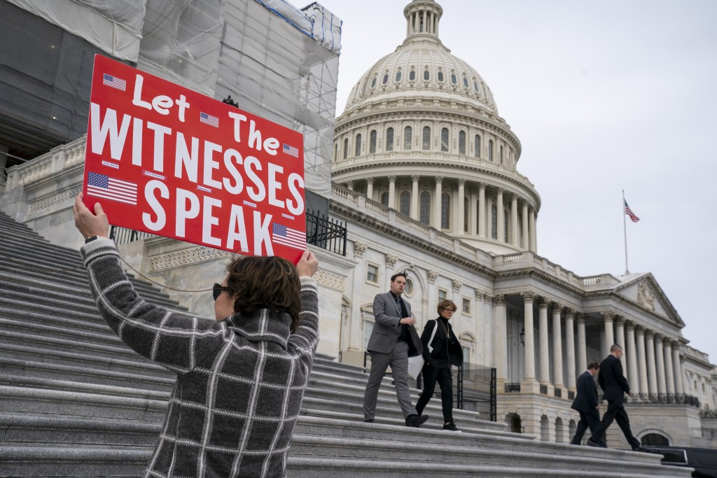 Laura Albinson of Pasadena, Md., displays a message for members of the House as they leave the Capitol in Washington, Friday, Jan. 10, 2020. House Spe...