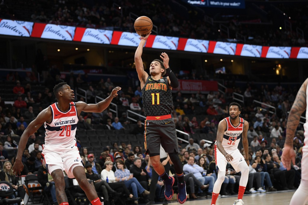 Atlanta Hawks guard Trae Young (11) goes to the basket next to Washington Wizards center Ian Mahinmi (28) and guard Jordan McRae (52) during the first...