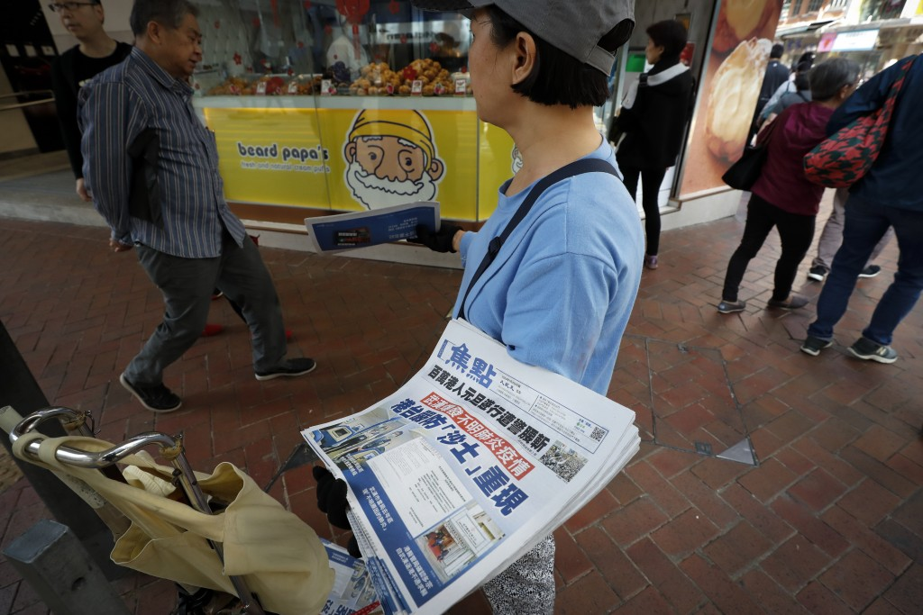 """A vendor gives out copies of newspaper with a headlines of """"Wuhan break out a new type of coronavirus, Hong Kong prevent SARS repeat"""" at a street in H..."""