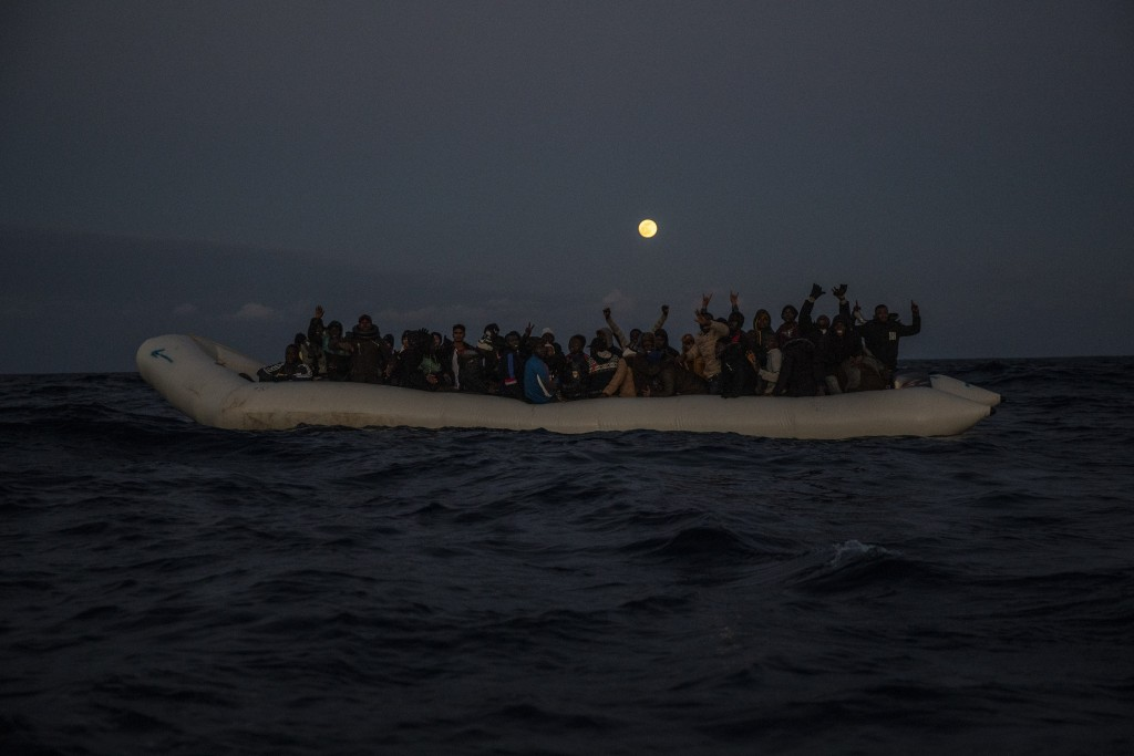 Migrants and refugees from different African nationalities react on an overcrowded wooden boat, as aid workers of the Spanish NGO Open Arms approach t...