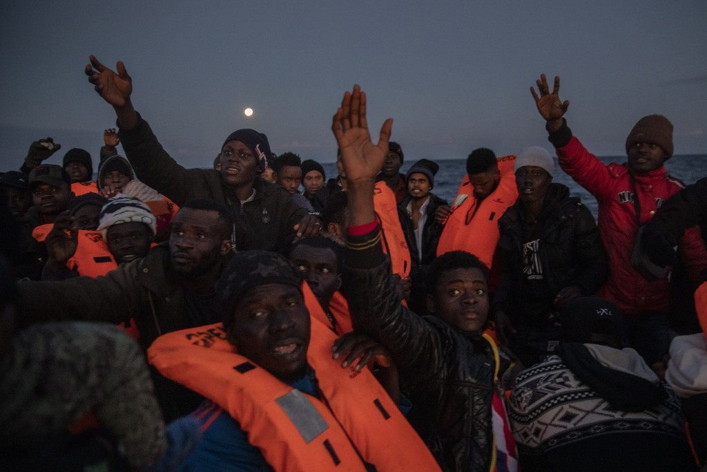 Migrants and refugees from different African nationalities sailing adrift on an overcrowded rubber boat, receive life jackets from aid workers of the ...