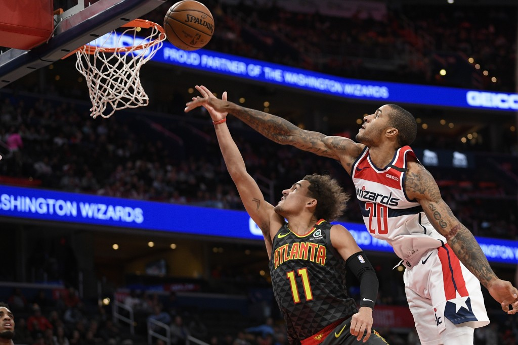 Atlanta Hawks guard Trae Young (11) goes to the basket next to Washington Wizards guard Gary Payton II (20) during the first half of an NBA basketball...