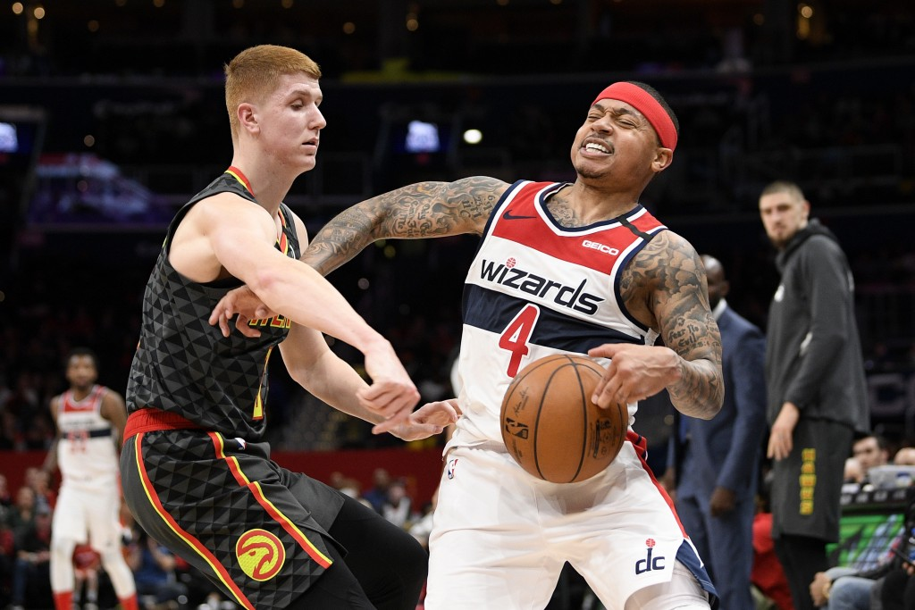 Atlanta Hawks guard Kevin Huerter (3) reaches for the ball next to Washington Wizards guard Isaiah Thomas (4) during the first half of an NBA basketba...