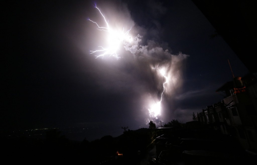 In this Sunday, Jan. 12, 2020, photo, lightning strikes beside the ash cloud as Taal Volcano erupts in Tagaytay, Cavite province, outside Manila, Phil...