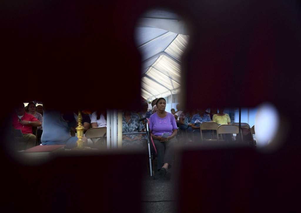 Seen through the cut-out shape of a cross on a priest's chair, a woman attends an outdoor Mass under a tent set up near the Immaculate Concepcion Cath...