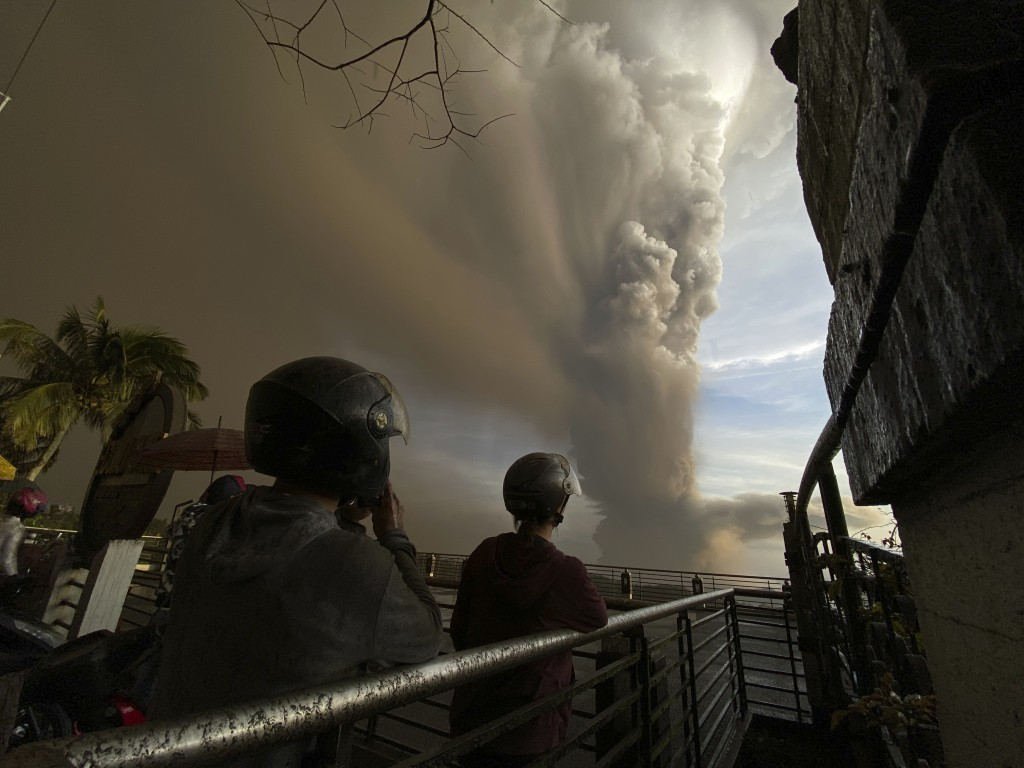 In this Jan. 12, 2020, photo, people watch plumes of smoke and ash rise from as Taal volcano erupts in Tagaytay, Cavite province, outside Manila, Phil...