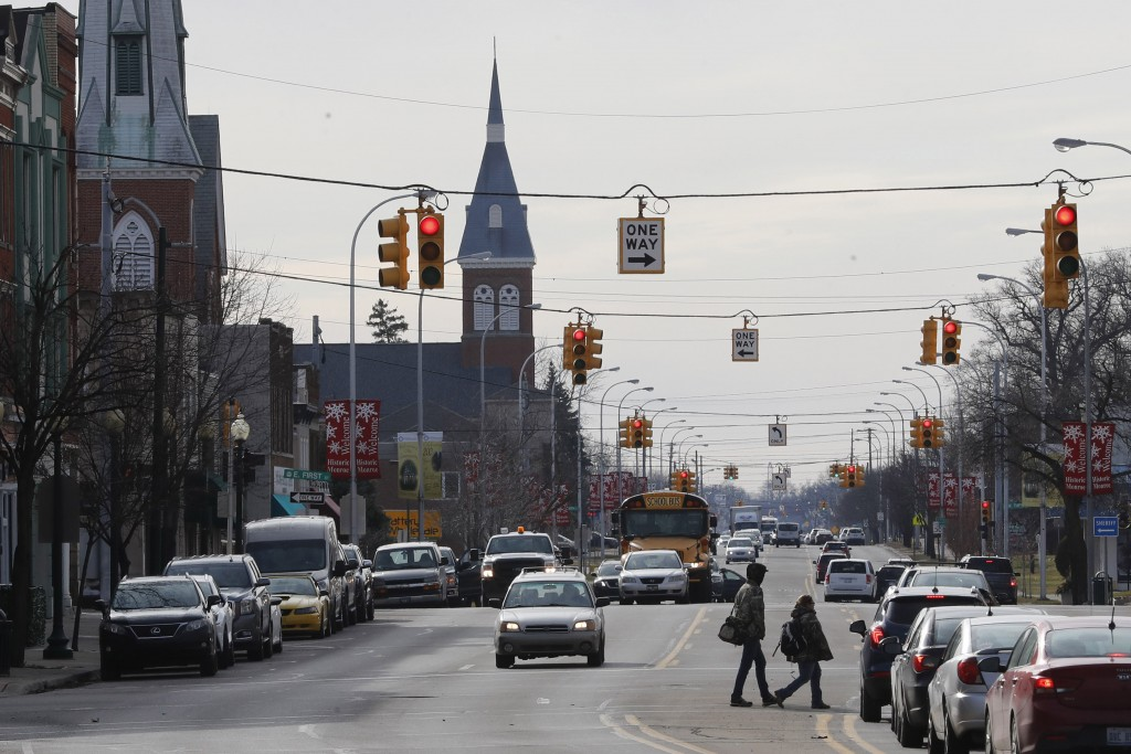 In this Tuesday, Jan. 7, 2020 photo, pedestrians cross S. Monroe St. in Monroe, Mich. Monroe County, population 150,000, has suffered six military cas...