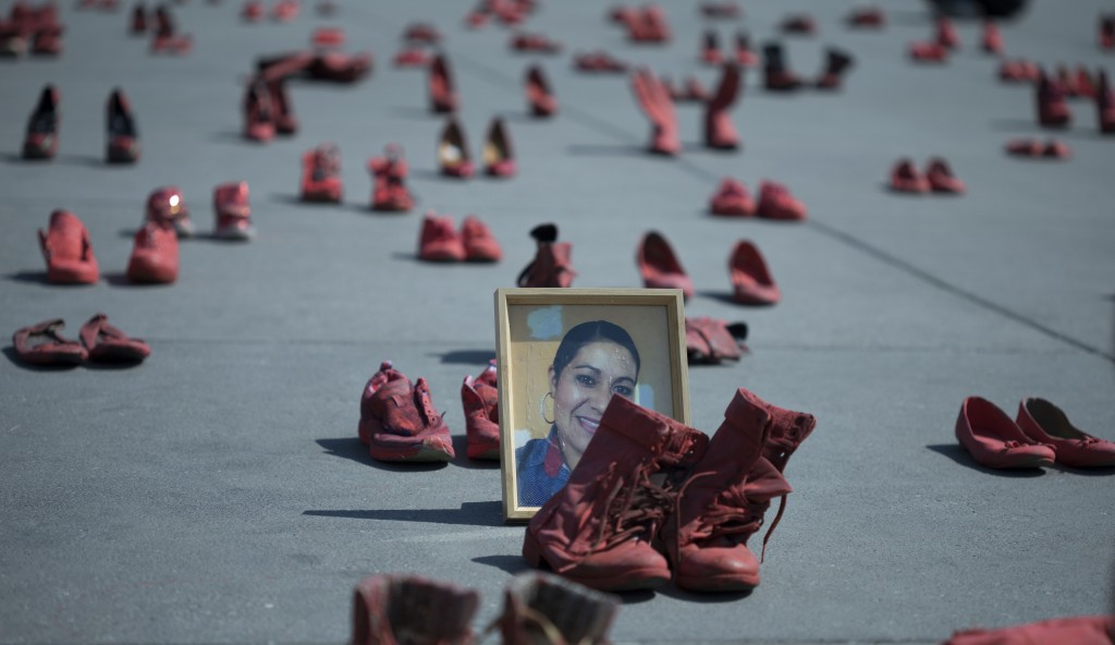 A portrait of Eugenia Machuca Campos sits amid women's red shoes placed by activists to protest violence against women in the Zocalo, Mexico City's ma...