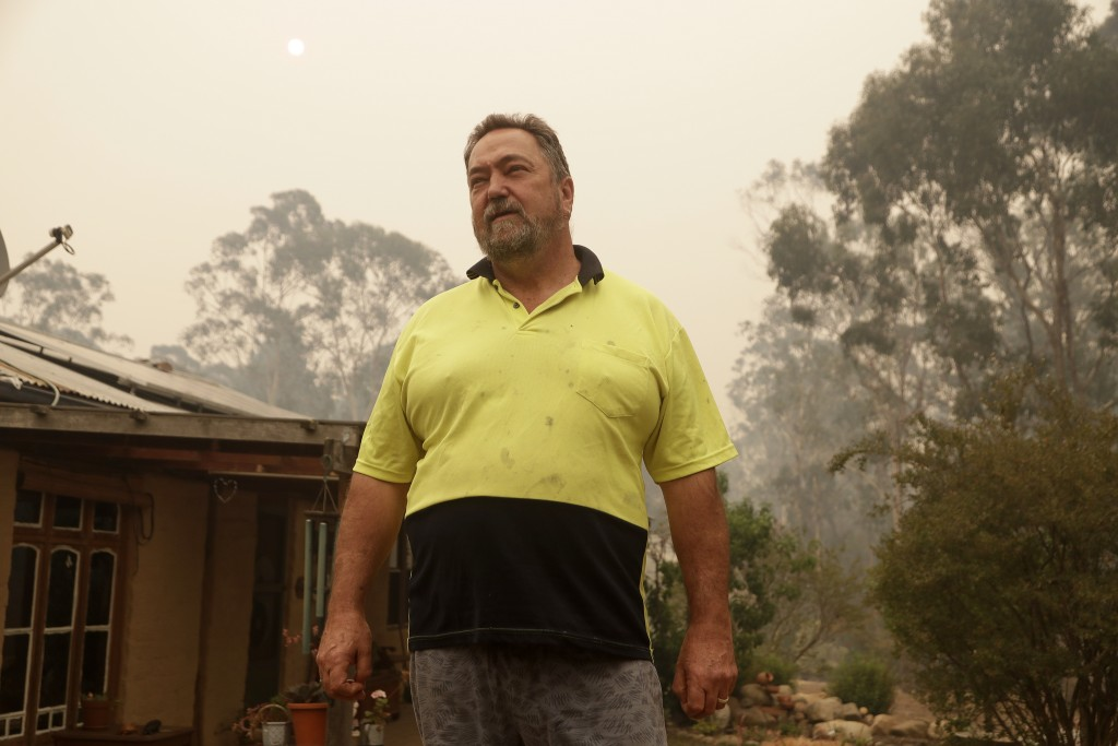 In this Jan, 11, 2020, photo, Joe Seamons stands outside his house at Burragate, Australiaa day after an anticipated wildfire impact failed to come. I...