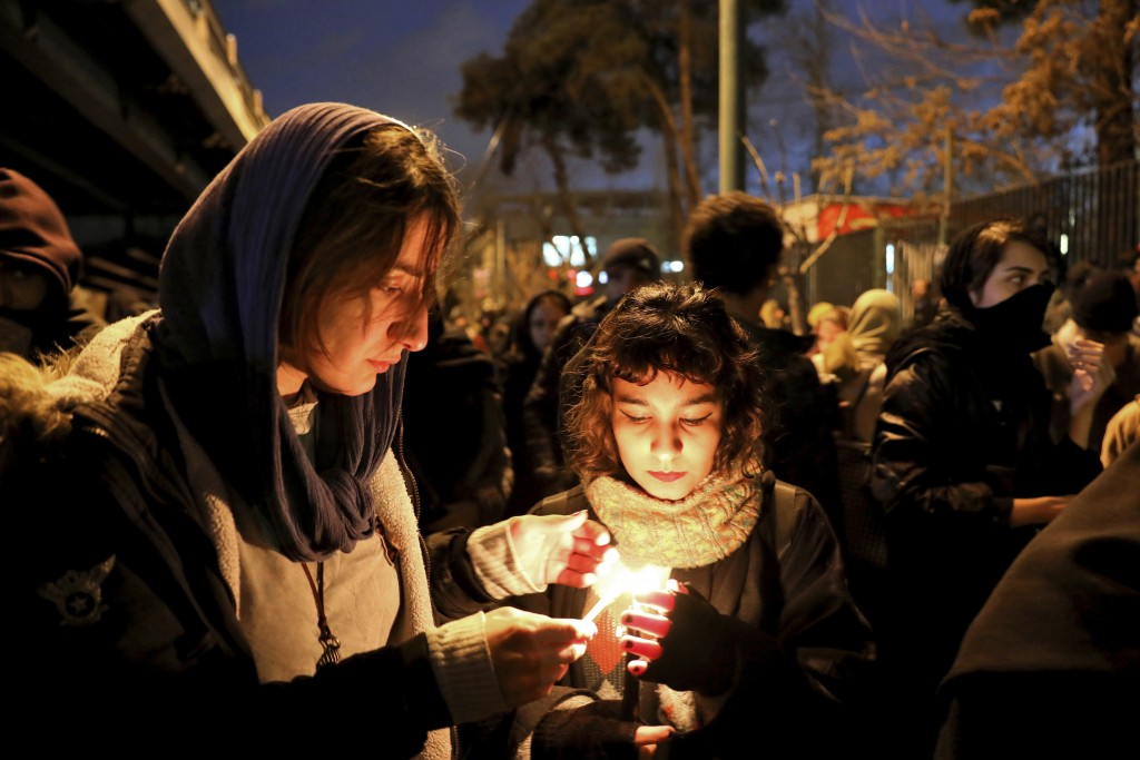 People gather for a candlelight vigil to remember the victims of the Ukraine plane crash, at the gate of Amri Kabir University that some of the victim...