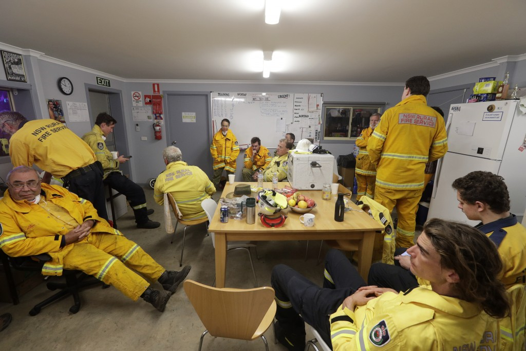 In this Jan. 10, 2020, photo, firefighters and army personnel gather in a common room at the Rural Fire Service fire house at Burragate, Australia. It...