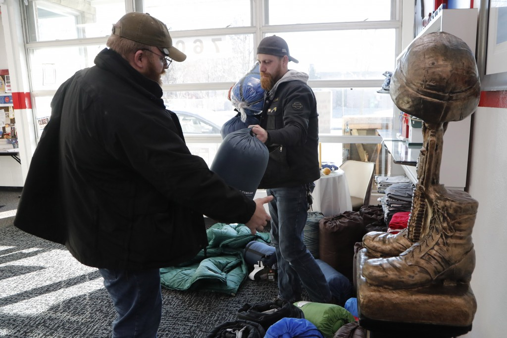 In this Wednesday, Jan. 8, 2020 photo, Larry Mortimer, left, helps Tim Fitzgerald load sleeping bags for the homeless at the Bedford Township Veterans...