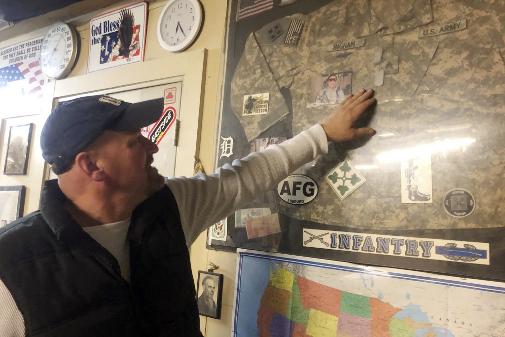 In this Wednesday, Jan. 8, 2020 photo, Michael Ingram touches the framed uniform of his son, Sgt. Michael Ingram Jr., as he talks about the 2010 death...
