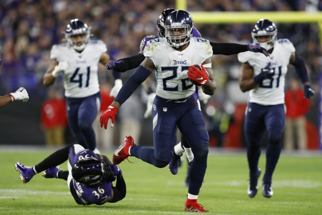 Tennessee Titans running back Derrick Henry (22) runs past Baltimore Ravens strong safety Chuck Clark (36) during the second half of an NFL divisional...