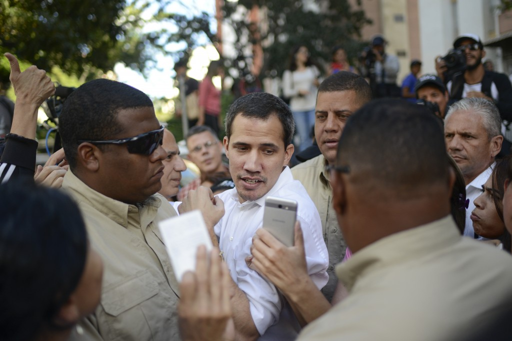 Bodyguards escort opposition leader Juan Guaido away from an outdoor event where he spoke to supporters in the Montalban neighborhood of Caracas, Vene...