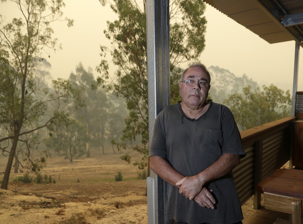 In this Jan, 11, 2020, photo, Joe Elvaro stands on the back deck his house at Burragate, Australia a day after an anticipated wildfire impact failed t...