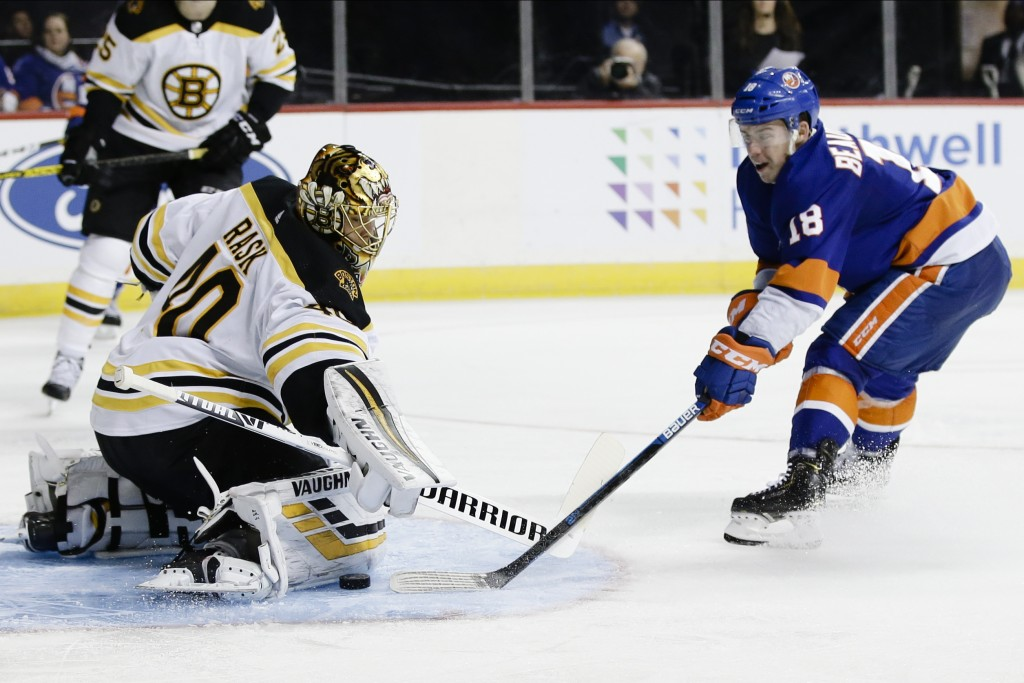Boston Bruins goaltender Tuukka Rask (40) stops a shot on goal by New York Islanders' Anthony Beauvillier (18) during the second period of an NHL hock...