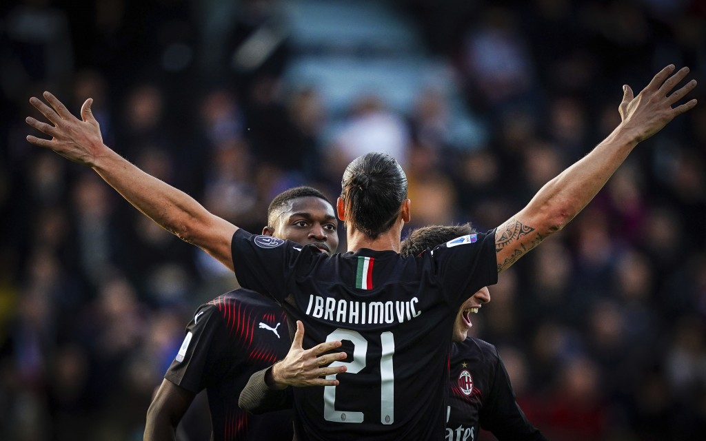 Milan's Zlatan Ibrahimovic celebrates with teammates after scoring his side's second goal during an Italian Serie A soccer match between Cagliari and ...