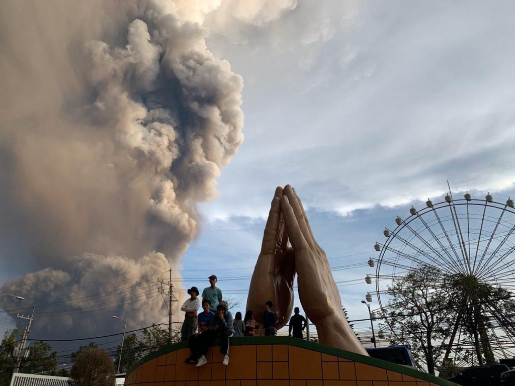 In this Sunday, Jan. 12, 2020, photo, people watch as the Taal volcano spews ash and smoke during an eruption in Tagaytay, Cavite province south of Ma...