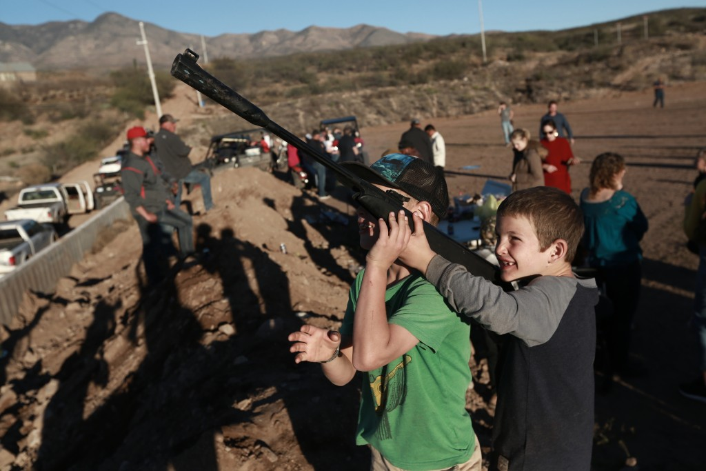 Boys point an unloaded gun at the sky as they play in La Mora, Mexico, one day before the expected arrival of Mexican President Andrés Manuel López Ob...