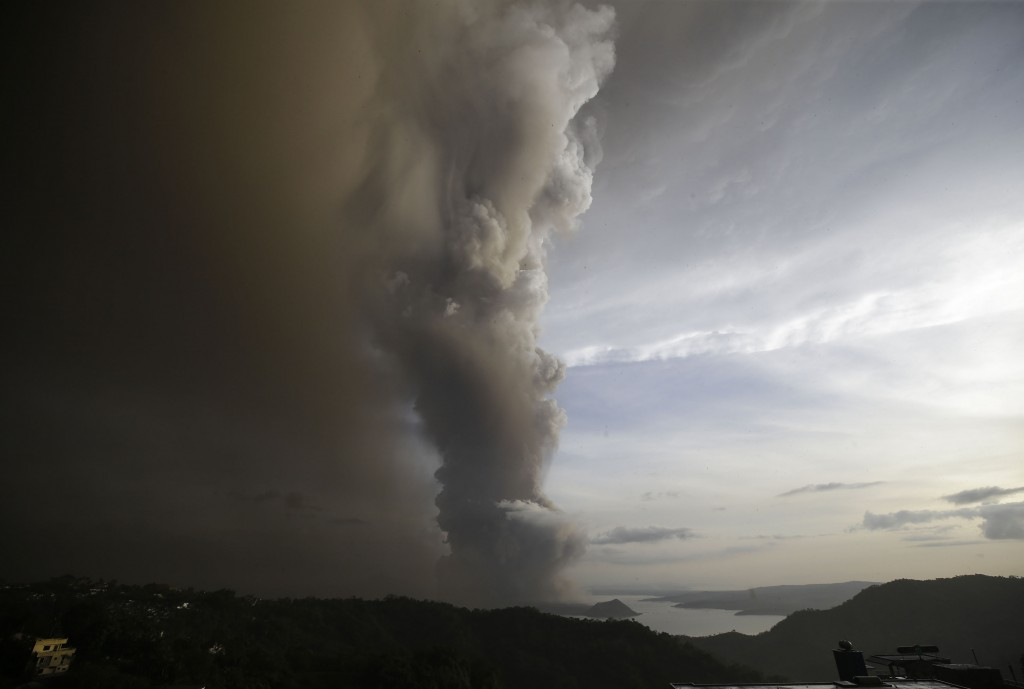 In this Sunday, Jan. 12, 2020, photo, Taal Volcano spews ash as it erupts, in Tagaytay, Cavite province, outside Manila, Philippines.  A tiny volcano ...