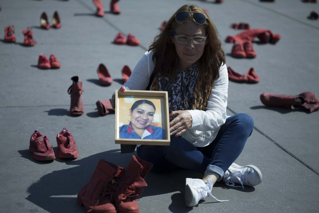 Elizabeth Machuca Campos holds the portrait of her sister Eugenia Machuca Campos amid women's red shoes placed in the Zocalo by people protesting viol...
