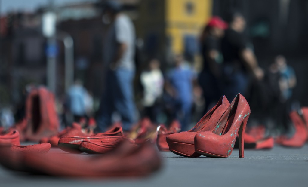 Women's red shoes are spread out in the Zocalo where they were placed by people to protest violence against women in Mexico City, Saturday, Jan. 11, 2...