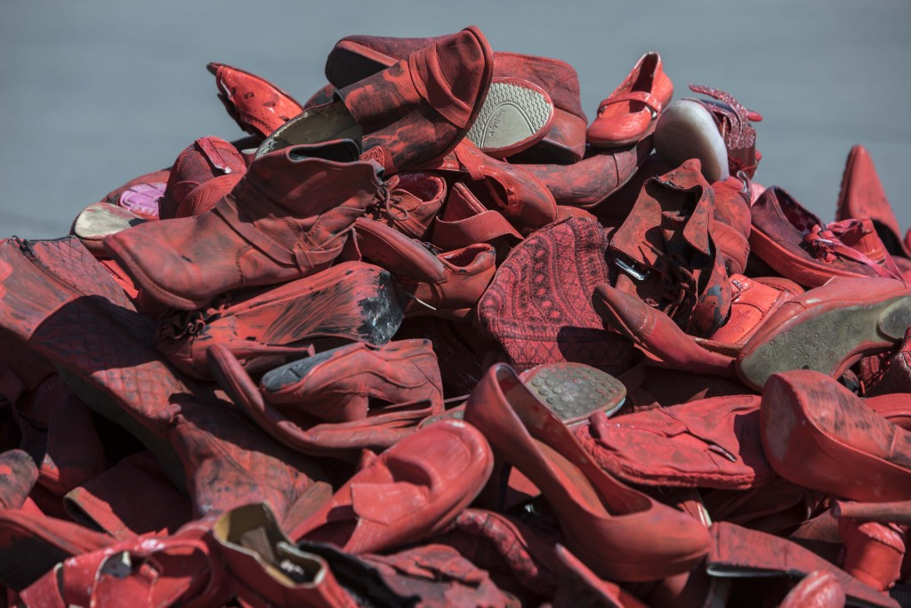 Women's red shoes are piled up in the Zocalo where they were placed by people to protest violence against women in Mexico City, Saturday, Jan. 11, 202...