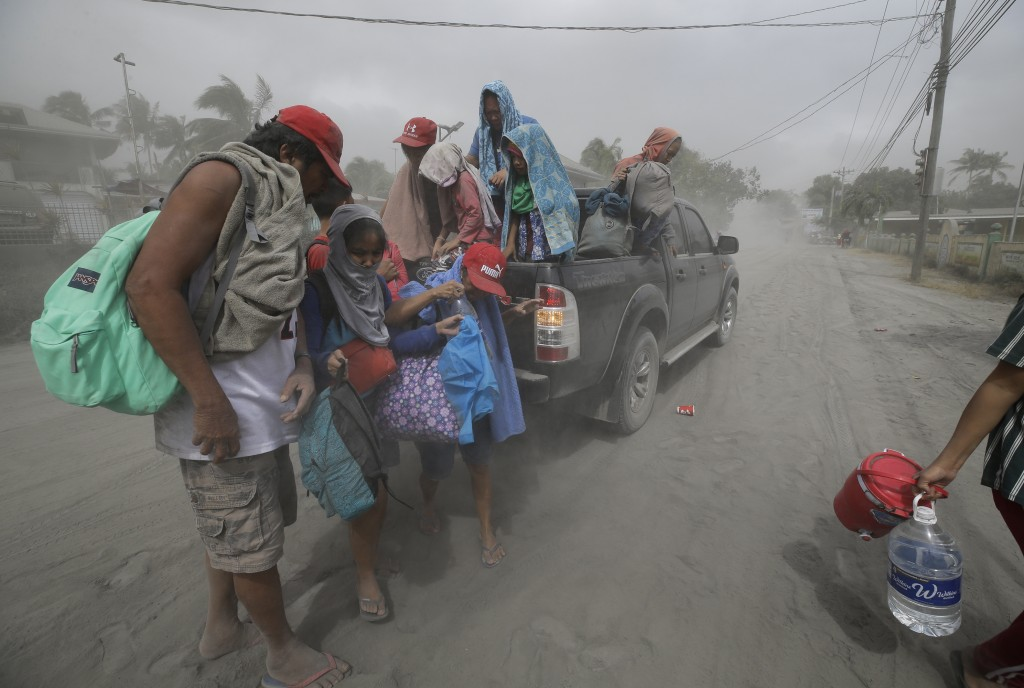 In this Monday, Jan. 13, 2020, photo,A family evacuates to safer grounds as Taal volcano in Tagaytay, Cavite province, southern Philippines. (AP Photo...