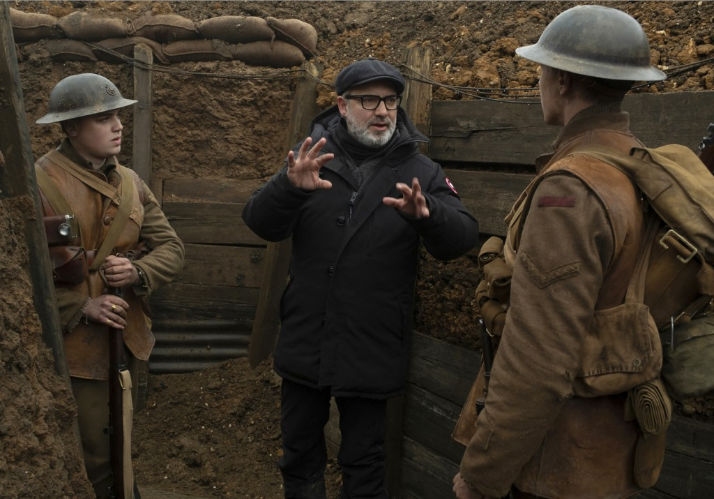 "This image released by Universal Pictures shows Dean-Charles Chapman, left, director Sam Mendes, center, and George MacKay on the set of ""1917."" On Mo..."