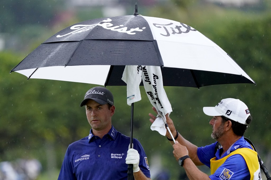 Webb Simpson keeps dry as his caddie dries off his club on the 13th green during the final round of the Sony Open PGA Tour golf event, Sunday, Jan. 12...
