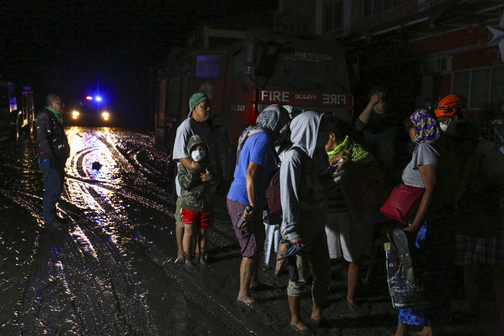 Residents wait to be evacuated as heavy ash and debris from the Taal volcano eruption cover their town in Talisay, Batangas, southern Philippines, Mon...