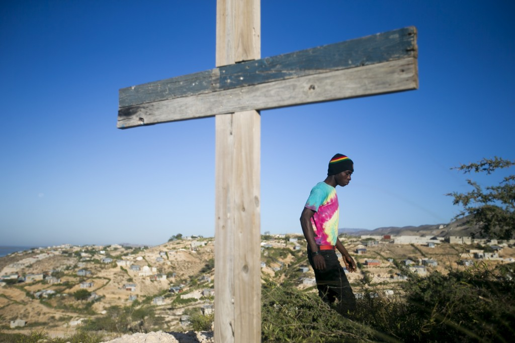 A resident walks past a cross during a memorial service honoring the victims of the 2010 earthquake, at Titanyen, a mass burial site north of Port-au-...