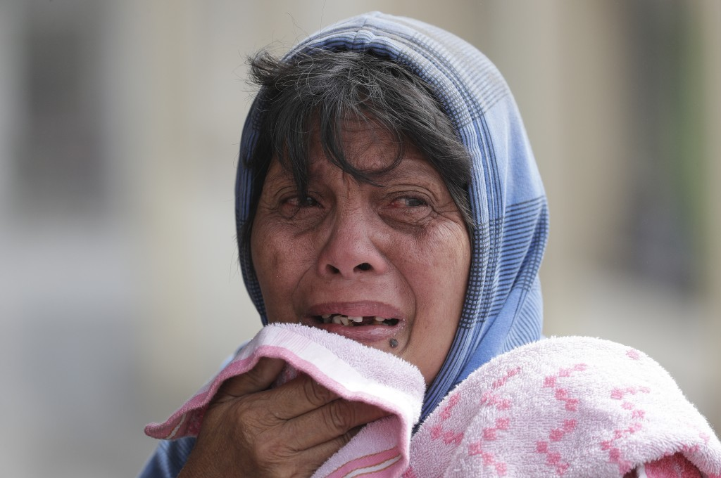 In this Monday, Jan. 13, 2020, photo, Erman Batan breaks in tears over her missing husband Roberto who she has not seen since they evacuated their hom...