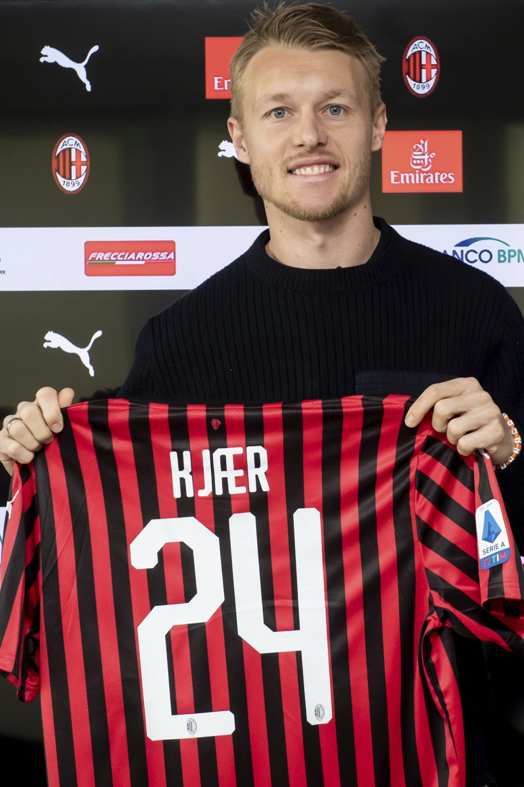 Simon Kjaer holds the AC Milan soccer club jersey as he poses for photographers during his official presentation at he club headquarters in Milan, Ita...