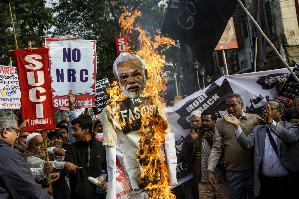 FILE- In this Jan. 11, 2020 file photo, members and activists Socialist Unity Center of India-Marxist (SUCI-M) burn an effigy of Indian Prime Minister...