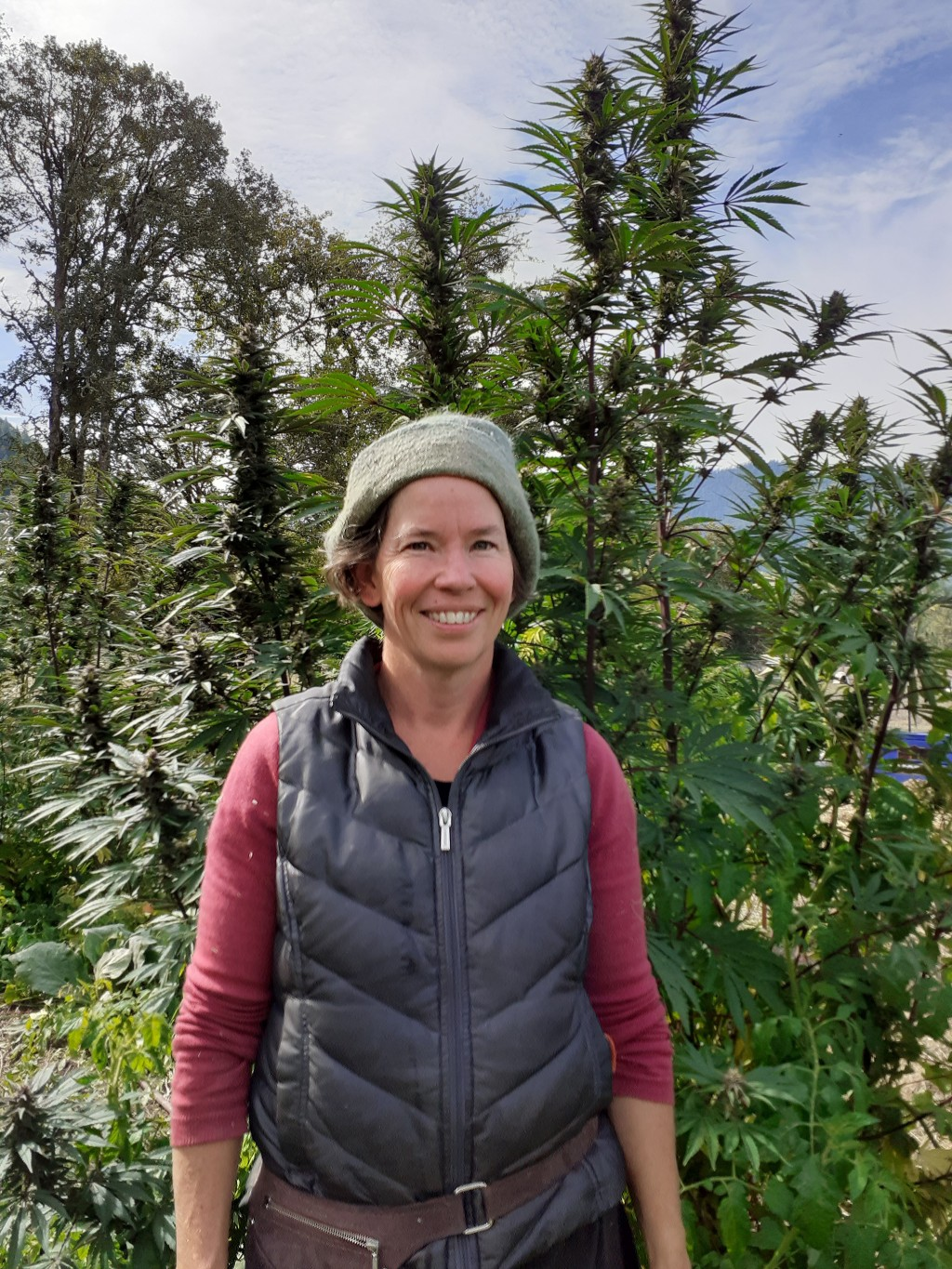 In this undated photo provided by Rosales CBD, Dove Oldham poses in front of a hemp plant growing at Madrona Family Farm in Grants Pass, Oregon. Oldha...