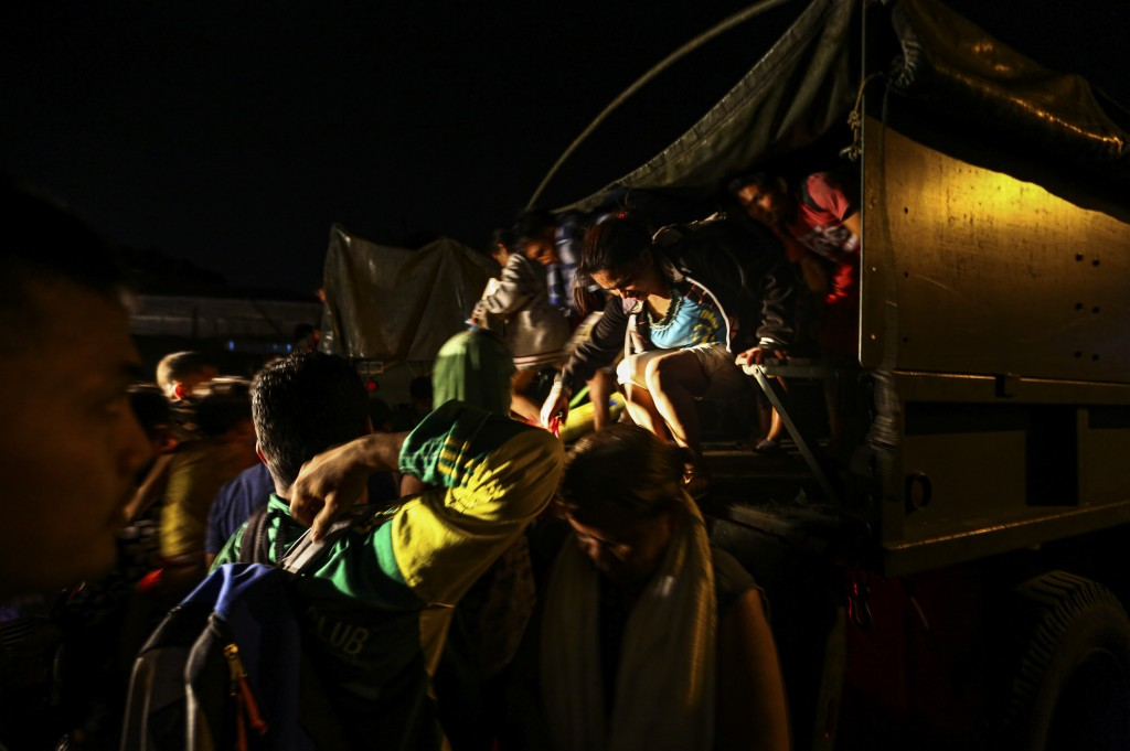Residents arrive in a military truck at a local school after being evacuated from the heavy ash  and debris from the Taal volcano eruption in Santo To...