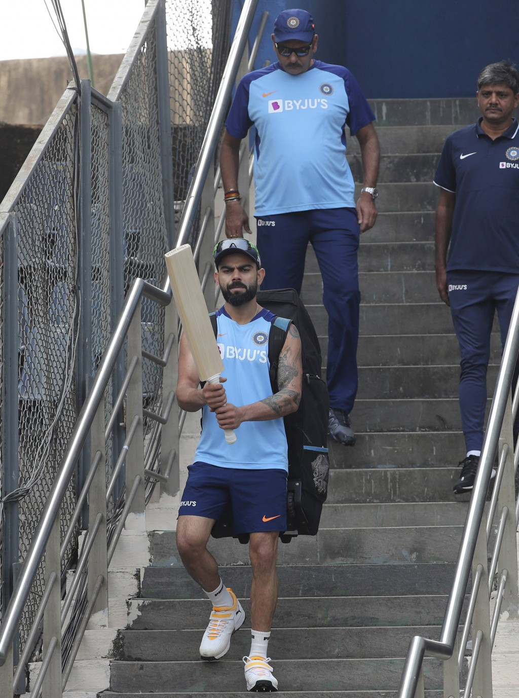 India's cricket captain Virat Kohli along with coach Ravi Shastri, behind, arrives for a training session ahead of their first one-day international c...