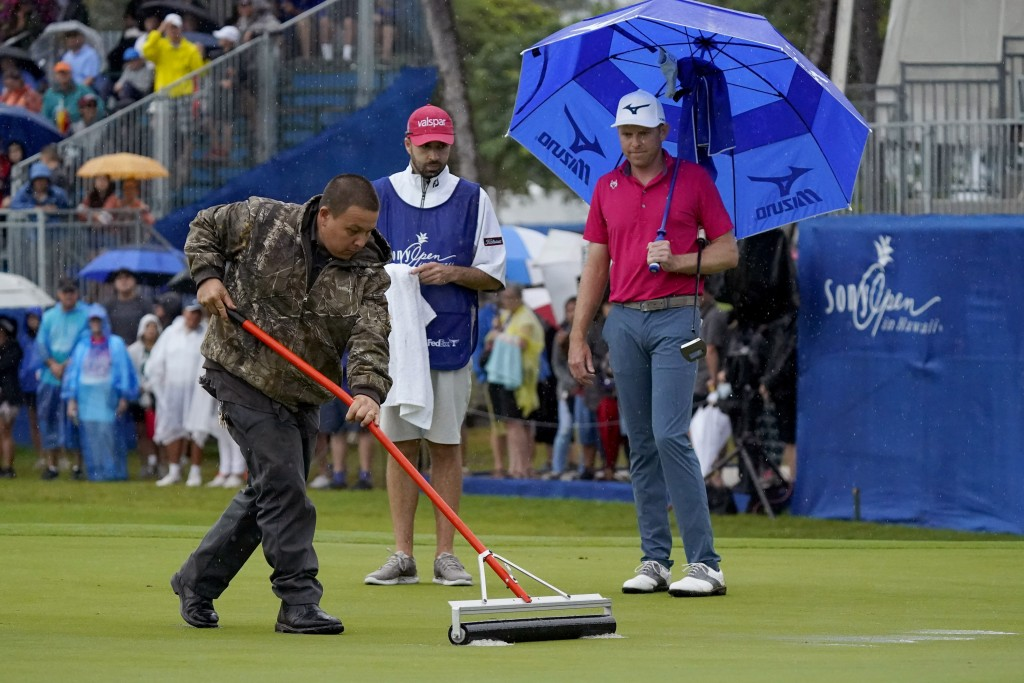 A course worker clears standing water off the 18th green before Bo Hoag putts during the final round of the Sony Open PGA Tour golf event, Sunday, Jan...