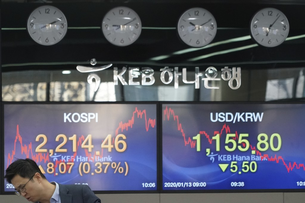 A currency trader reacts while he speaks with his colleague near the screens showing the Korea Composite Stock Price Index (KOSPI), left, and the fore...