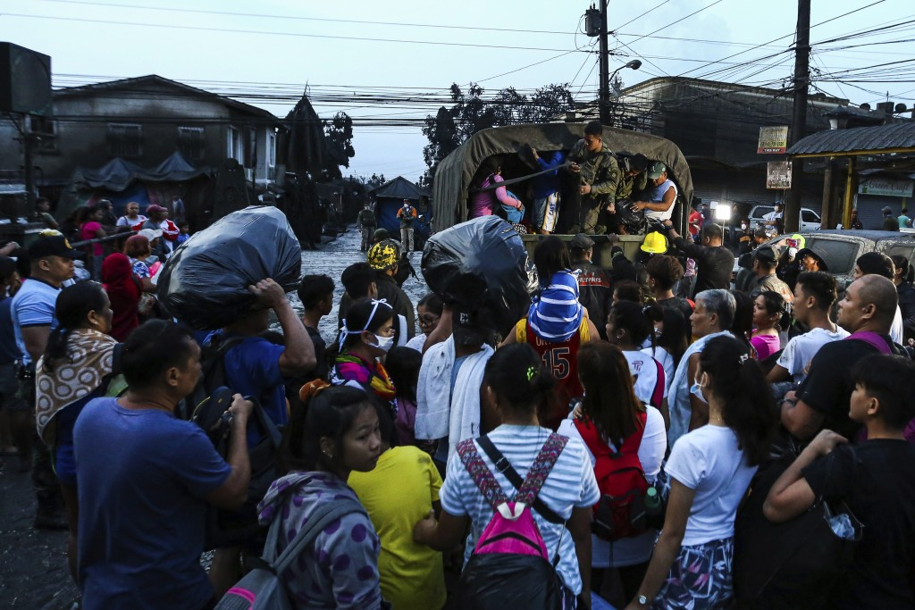 Residents wait to be evacuated as heavy ash and debris from the Taal volcano eruption continues to cover their town in Talisay, Batangas, southern Phi...