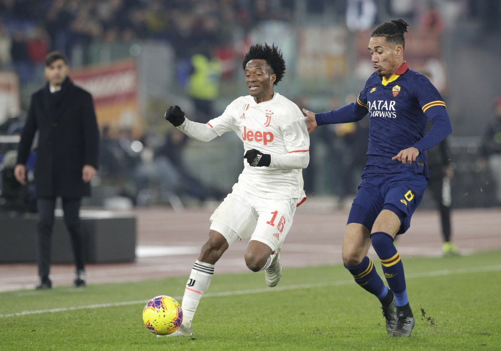 Juventus' Juan Cuadrado, centre, and Roma's Chris Smalling challenge for the ball during the Serie A soccer match between Roma and Juventus at the Rom...