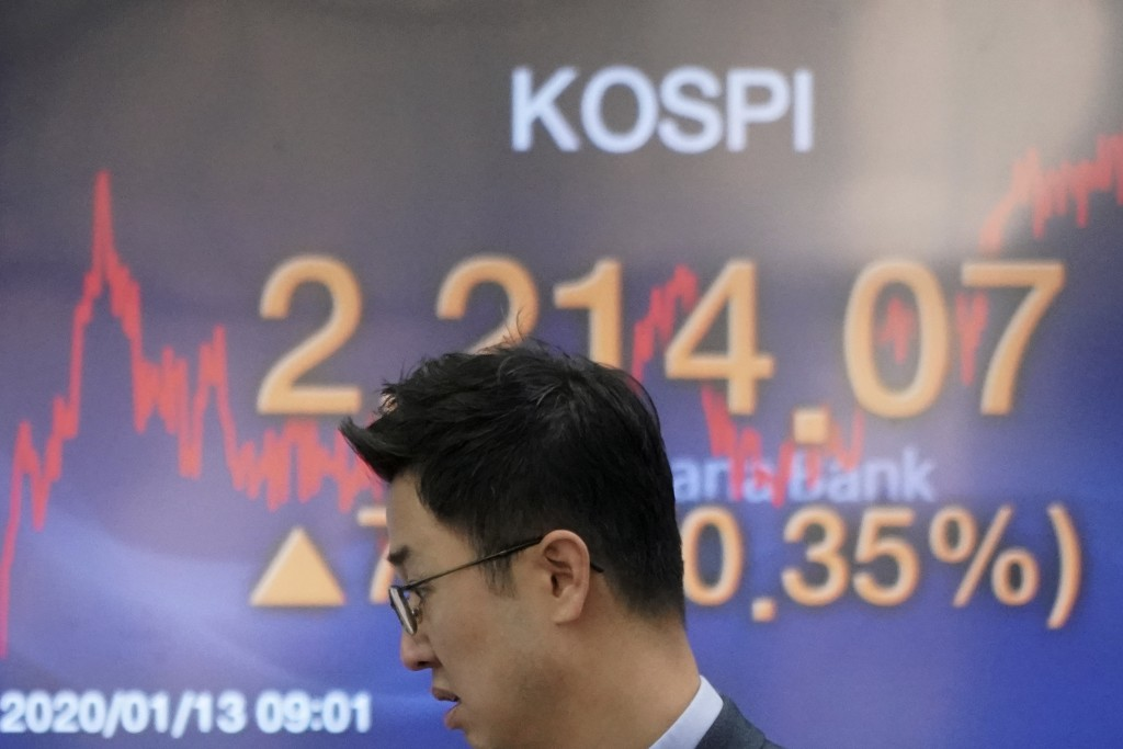 A currency trader walks by the screen showing the Korea Composite Stock Price Index (KOSPI) at the foreign exchange dealing room in Seoul, South Korea...