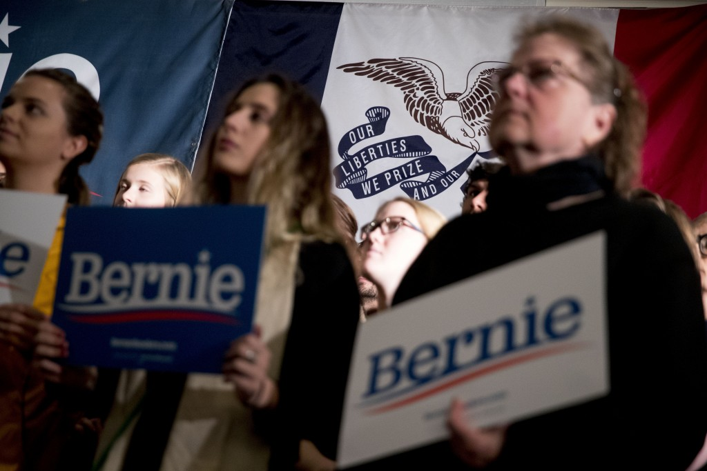 Members of the audience hold campaign posters in front of the Iowa state flag before Democratic presidential candidate Sen. Bernie Sanders, I-Vt., arr...