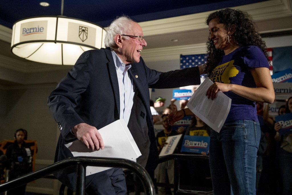 Democratic presidential candidate Sen. Bernie Sanders, I-Vt., left, is welcomed to the stage by Sunrise Movement co-founder Varshini Prakash, right, a...