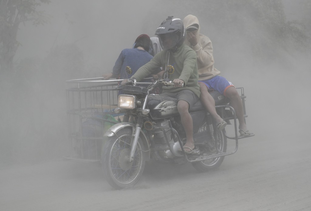 In this Jan. 13, 2020, photo,  a family rides their motorcycle through clouds of ash as they evacuate to safer grounds as Taal volcano in Tagaytay, Ca...